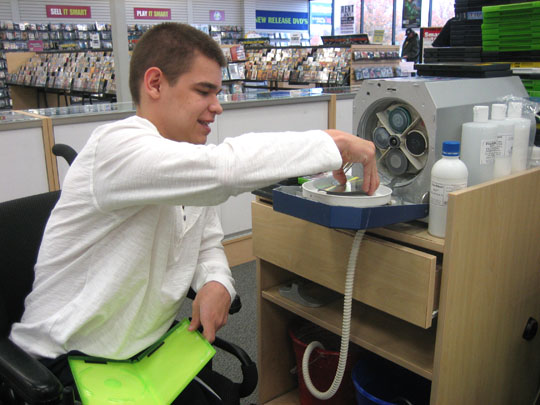 Youth who is a wheelchair user puts a CD in a machine to be cleaned