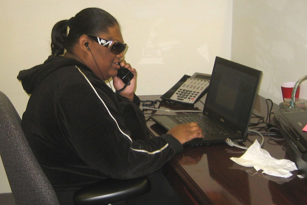Intern Laridda talks on the phone while at her desk
